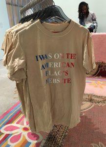 """T-Shirts mit Aufdruck; im Hintergrund ein """"Verkäufer"""". Foto © Rose Wagner"""