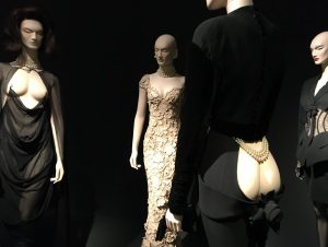 """Links Haute-Couture-Kleid, dessen Träger mit Piercings an den Brustwarzen befestigt werden; im Vordergrund Etuikleid mit """"derrière décolleté"""" aus der Kollektion 1995/96. Foto © Rose Wagner"""